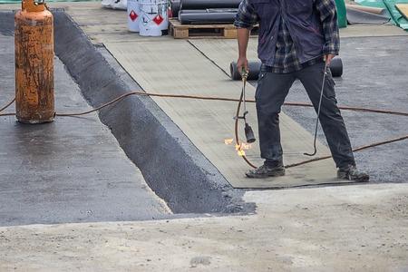 בעל מקצוע אוטם את הגג עם יריעות